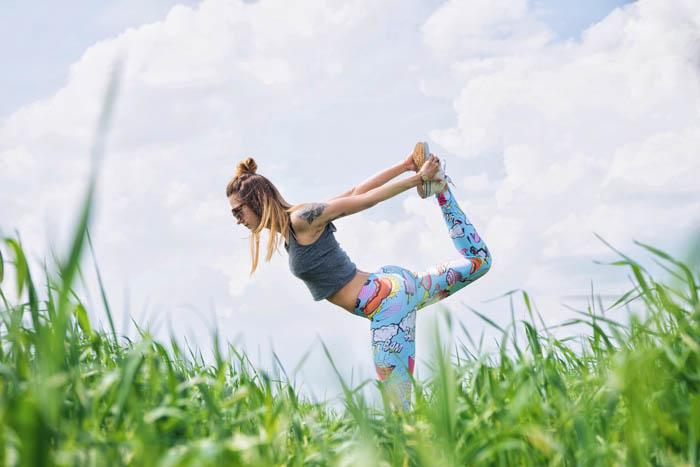 una chica en el campo realizando un ejercicio de estiramiento y queda en equilibrio sobre una pierna. La otra pierna la coge con las manos por detrás