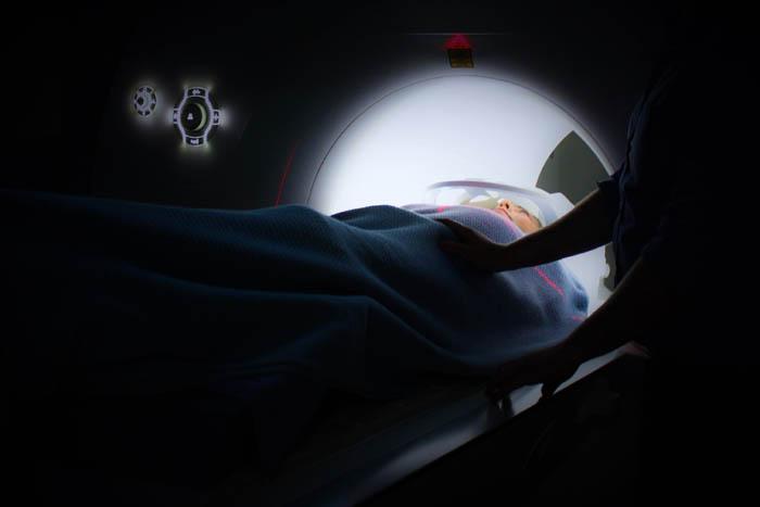 se trata de una persona dentro de una máquina a la cual le están realizando un tac con un médico a su lado