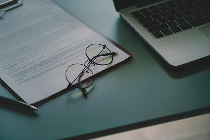 Escritorio con informe médico, ordenador portátil y unas gafas