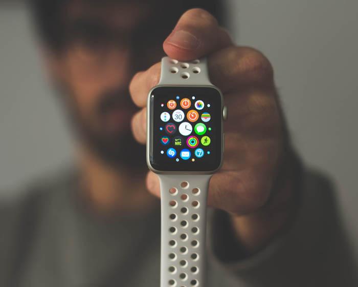 Un apple watch con sus diferentes aplicaciones en la pantalla y una persona sujetándolo en el fondo por su mano